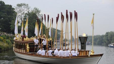 The Flame travels down the Thames on board the Royal barge Gloriana en route to the Olympic Stadium...