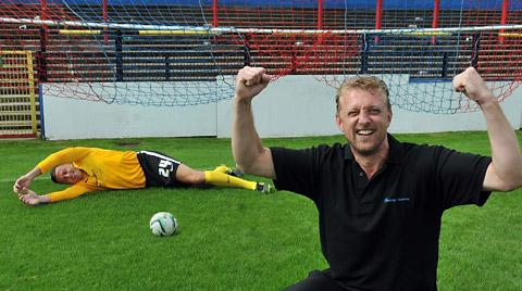 Mark McLoughlin, of cleaning  company Synergy, tests York City 'keeper Michael Ingham at the club's photocall at Bootham Crescent