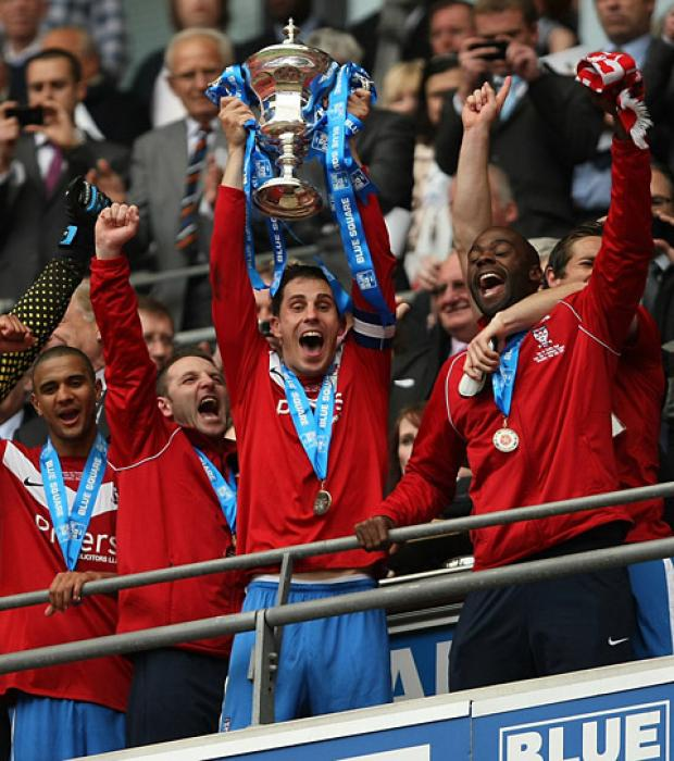 Chris Smith hoists aloft the Blue Square Bet Premier play-off final trophy at Wembley. Picture: Gordon Clayton