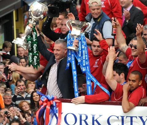 York City manager Gary Mills wields the club's two Wembley trophies on May's triumphant open top bus tour
