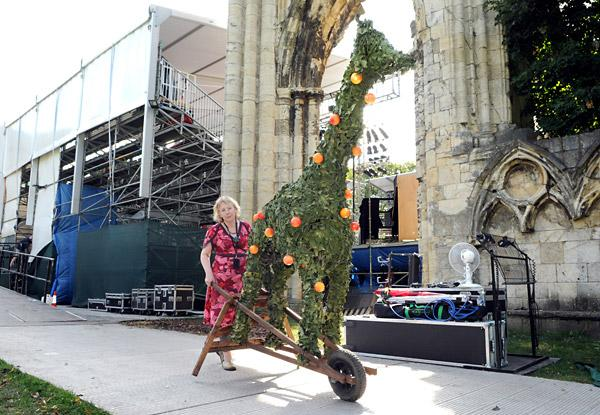 Jo Keogh, a member of the backstage production team, wheels away a topiary giraffe from the set of the Mystery Plays after the last performance
