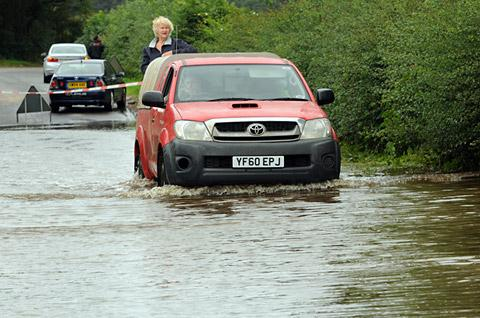 A vehicle drives through flood waters on the Buttercrambe Road near Stamford Bridge. Other cars, seen in the background, failed to make it and had to wait for assitance and recovery