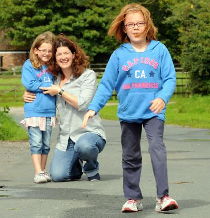 Willow Emmison-Neal demonstrates her walking ability earlier this year, as her mother Sally and  sister Olive look on