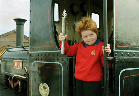 Six-year-old Charlie Holtby, of the Boys' Brigade 1st Acomb Company, holding the Baton, during the handover at the National Railway Museum, on the footplate of steam locomotive Lilla