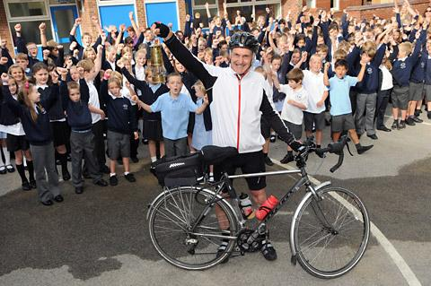 Brian Saynor is cheered on his way by pupils at Stamford Bridge Primary School