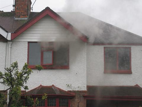 Smoke pours from an upstairs window