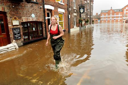 Natalie Stroughair wades through flood water in Cumberland Street