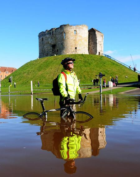 A cyclist wades through floodwater by Clifford's Tower, York.