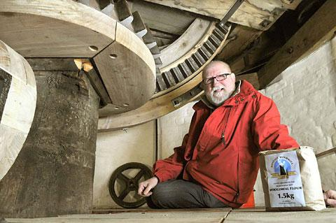 Bob Anderton, who has worked on the mill since its restoration, sits in the engine room at the top of Holgate Windmill with a bag of flour