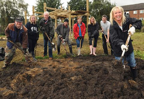 A group of  volunteers from York businesses dig over a section of the York Cares Big Community Challenge site at Greenfields, off Haxby Road