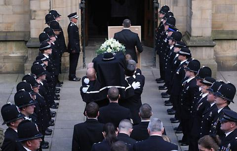 The coffin of PC Nicola Hughes, one of the two policewoman murdered in Manchester on September 18, is carried into Manchester Cathedral for her funeral service as colleagues from Greater Manchester Police form a Guard of Honour