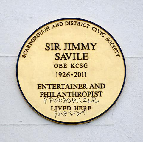 The plaque which has been defaced on the wall outside Sir Jimmy Savile's former home in Scarborough