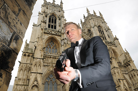 James Bond lookalike Steve Wright strikes a typical 007 pose in front of York Minster