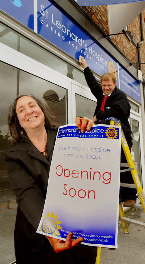 Shop manager Maria Aebi and Martin Stephenson, of Dayfield Graphics, put the finishing touches to the new St Leonard's Hospice furniture shop in Heworth