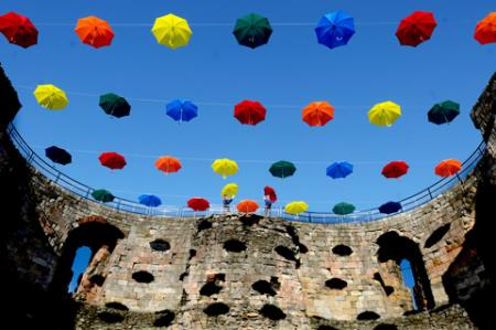 An art installation consisting of 45 umbrellas makes a colourful canopy across Clifford's Tower in York.