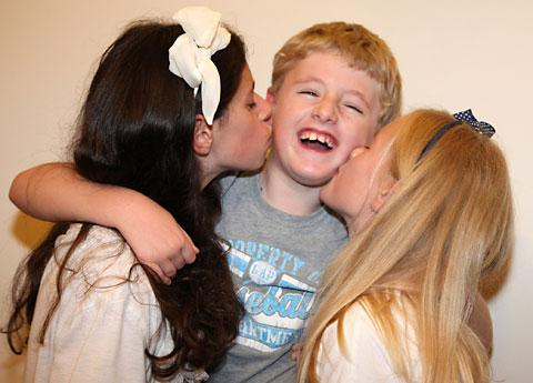 Aimée and Katie Swan, aged 13 and 10, give their younger brother Ethan, a kiss