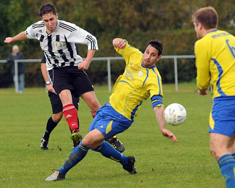 Dunnington striker Scott Sullivan, left, fires in a shot which is blocked by Huntington Rovers defender Dave Hartas, but he went on to find the net in his side's 2-1 win