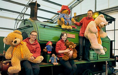 NRM staff, from left, Hannah Mathews, Jen Sharp and Noel Hartley sit on the locomotive Teddy with some of the visiting bears