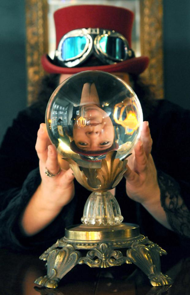 "York's ""Ghostfinder General"", Rachel Lacy, looks through a crystal ball in the dining room at the Haunted House in Stonegate"