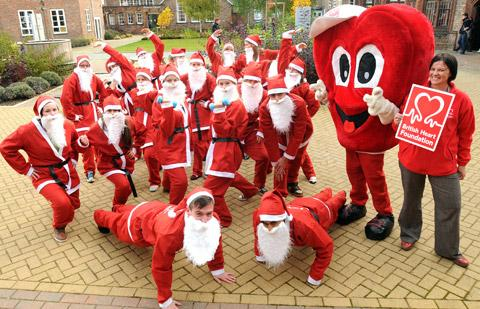 "Vicky Hearson, right, of the British Heart Foundation, looks on as the ""Santas"" limber up at the launch of annual Santa Jog at York St John University"