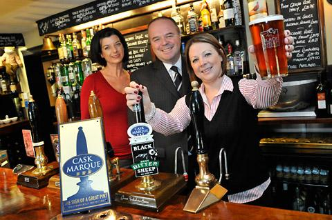 Kate Mackenzie from the Pipe and Glass Inn raises a glass to celebrate receiving the Cask Marque, She is watched by cask beer inspector Annabel Smith and Phil Bebbington, national account manager for Black Sheep Brewery