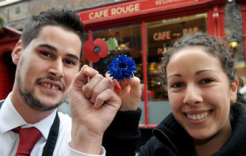 Sandrine Bauchet, of the Yorkshire Air Museum, holds a bluets and Alexis Menendez, of Café Rouge, with a poppy, outside the restaurant in Low Petergate, where both  flowers of remembrance are available