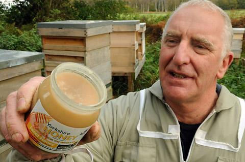 Beekeeper Paul Snowden with the honey ruined after his bees feasted on fondant