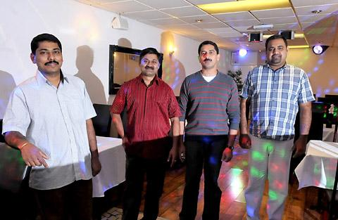 Sanjai Joseph, left, and chef Saji Kurian with former taxi drivers Dinu Abraham and Jaico Jose in the Coconut Lagoon restaurant in Clarence Street