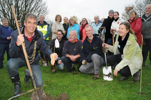 The Lord Mayor of York, Keith Hyman, plants the sapling at Willow Bank in New Earswick, as part of a scheme in which volunteers, some of whom are pictured, planted 420 trees