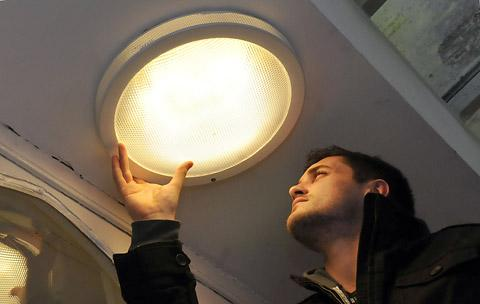 Tom Holmes from St Michael le Belfrey Church changes a light bulb for a neighbour