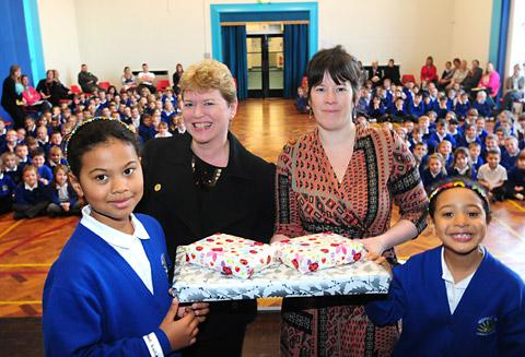 Jo Whitehouse, City of York Council housing officer, presents prizes to Westfield School pupils Phoebe and Olivia Konadu, who designed a logo promoting a new advice service, watched by head teacher Tracey Ralph, second left