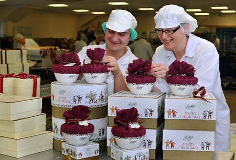Justin Clapham and Julie Adams finish off the bows on Bettys Christmas puddings ready for despatch