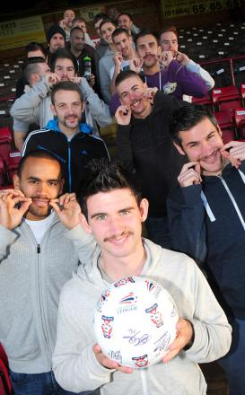 Paddy McLaughlin, front, heads his York City team-mates as they show off their moustaches, which they have been growing for 24 days to raise money for Movember. They have so far raised more than £850