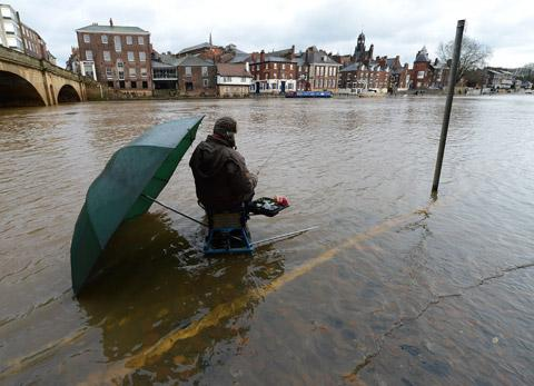 An angler takes advantage of the rising                  floodwater in York on Queen's Staith