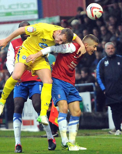 York City man of the match Danny Kearns is beaten to the ball by Torquay's Ryan Jarvis as manager Gary Mills looks on