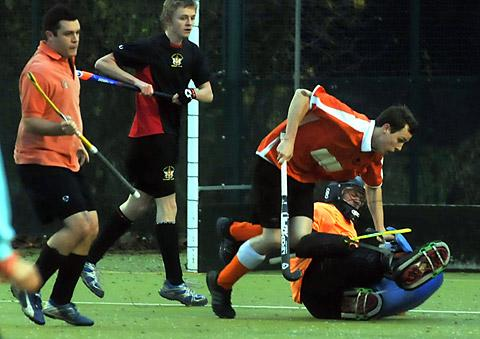 Acomb Hockey Club's Ryan Forster collides with the Bradford University 'keeper
