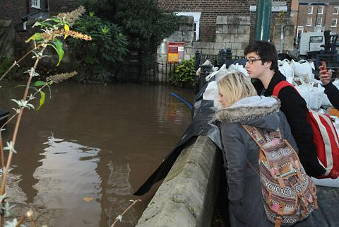 Passers-by observe the rising waters at Tower Gardens, York