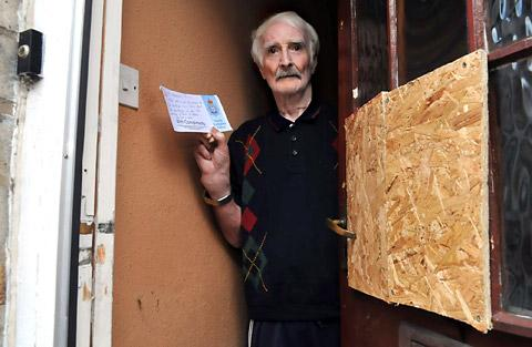 Ken Eggleton, 74, with the note left by police after his front door was broken down last month