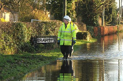 Yorkshire Water engineers walk through the floodwater at Brawby
