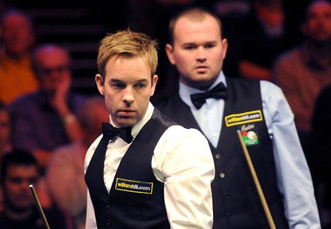 Mark Joyce looks over Ali Carter's shoulder during their match in the UK Snooker Championship