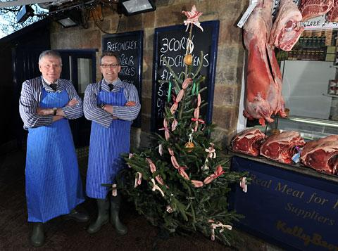 Peter Buck, owner and master butcher of Hutchinson's of Ripley, and his manager and butcher, Nick Allen, with their Christmas tree decorated with garlands of chipolata sausage, streaky bacon tinsel and topped with streaky bacon star