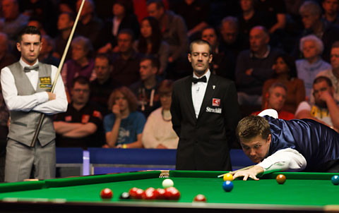 Mark Selby, left, looks on as round two opponent Ryan Day, right, takes aim at the Barbican