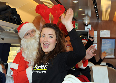 The 'flash mob' singers, above and inset, burst into song on board an East Coast train in aid of The Railway Children charity