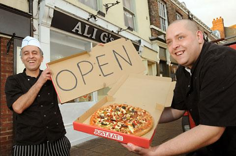 Ali Gurgur, left, and Simon Dix                     celebrate the reopening of Ali G's in Tower Street, York, after it was badly                    damaged by            flooding in September