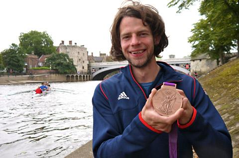 Tom Ransley shows off his bronze medal on a visit to York City Rowing Club