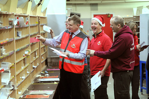 YORK Central MP Hugh Bayley, left, helps out at Royal Mail's Leeman Road sorting office watched by postman Phil Harvey and CWU branch secretary Keith Blackburn, right