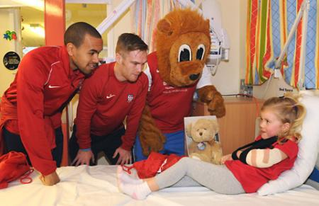 Ashley Chambers, left, Jason Walker and Yorkie the Lion chat to a young patient on the children's ward at York Hospital.