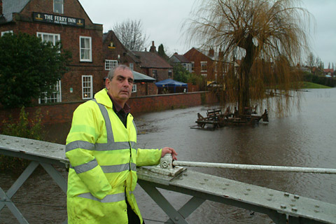 Flood     warden David Jones  monitors the river level at Cawood Bridge. Picture: Eric Foster