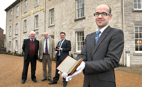 Restaurant manager Dominique Ghislain with the edition of A Christmas Carol at The Talbot Hotel, Malton, watched by, from the left, Malcolm Chalk, left, of the town's Dickens Society,  businessman Stephen Joll and Robert Wormall, Talbot manager