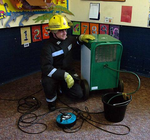 Firefighter Mark Bond, of Huntington fire station, helps with the clean-up operation at the Fire Station playgroup in Malton